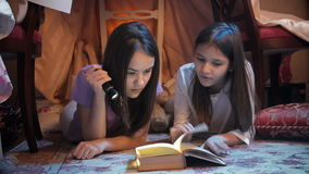 4k video of two girls reading book with flashlight in teepee tent stock video