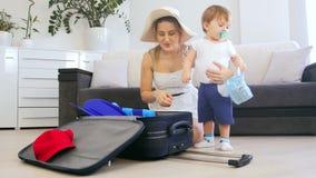 4k video van aanbiddelijke peuterjongen die de dingen van de moederverpakking in koffer helpen stock videobeelden