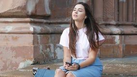 4k video van beuatiful donkerbruine vrouwenzitting op straat en het luisteren muziek met oortelefoons stock video