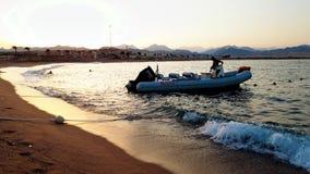 4k video van de jonge mens die zijn boot schoonmaken bij zonsonderganglicht stock footage