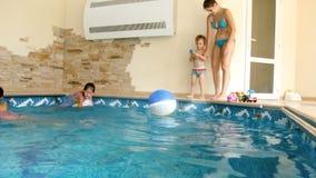 4k video van gelukkige familie die pret hebben en bij binnen zwembad bij hotel spelen stock video