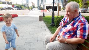 4k video van grootvader met kleinzoon lanceringsstuk speelgoed helikopter op bank bij park stock footage