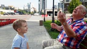 4k video van het hogere grootvader spelen met zijn peuterkleinzoon met stuk speelgoed op bank bij park stock video