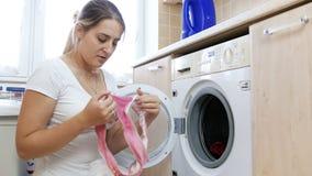 4k video van jonge die vrouw tot fout door verschillende kleurenkleren wordt gemaakt in wasmachine samen te brengen stock footage