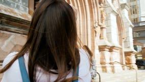4k video van mooie donkerbruine vrouw die foto's van oude kathedraal maken bij Europese stad stock video