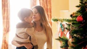 4k video van mooie jonge moeder die haar omhelzen weinig jongen en Kerstboom in woonkamer bekijken stock video