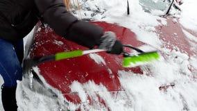 4k video van mooie vrouwelijke bestuurder die haar auto van sneeuw na blizzard schoonmaken bij ochtend stock footage
