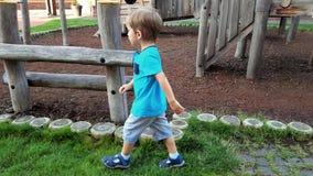 4k video van weinig peuterjongen die bij park met grote houten kinderenspeelplaats lopen stock videobeelden