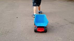 4k video van weinig peuterjongen die en stuk speelgoed vrachtwagen lopen trekken door kabel stock footage