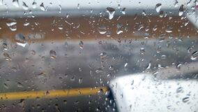 4k video through wet window on airplane accelerating on runway to take off during heavy rain and strong wind