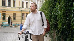 4k video of young bearded man walking next to vintage bicycle on old town street. 4k footage of young bearded man walking next to vintage bicycle on old town stock video