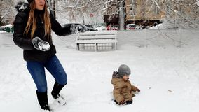 4k video of young mother playing with her toddler son in winter park and throwing snowballs stock video footage