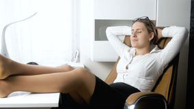 4k video of young businesswoman relaxing at office and holding legs on desk