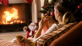 4k footage of young woman knitting wool scarf at burning fireplace and Christmas tree