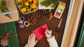 Top View of Hands Putting a Postcard in Envelope and Writing Christmas Greetings. 4K View from Above of Female Hands Putting the Postcard in an Envelope and Royalty Free Stock Photos