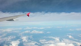 4K View from airplane window flying above the clouds stock footage