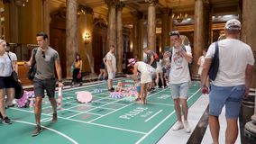 4k Visitors, Tourists, families and children play on giant roulette table in the lobby of the famous Monte Carlo Casino