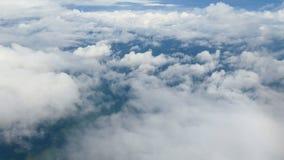 4K vista aerea attraverso una finestra dell'aeroplano belle nuvole bianche nel fondo del cielo blu Viaggiando dall'aria video d archivio