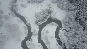 4K Vlucht boven wolken en wilde windende rivier in de bevroren bossnowly-winter op het noorden Lucht panorama stock videobeelden