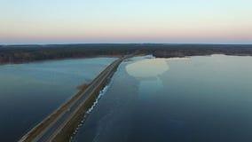 4K Vlucht over weg in het bevroren meer in de winter op zonsondergang, luchtmening stock video