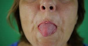 4k - Volwassen vrouw die tong, haar mond tonen dicht, langzame motie stock video
