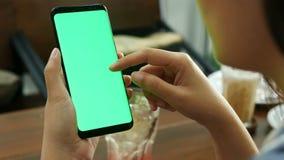 4K vrouw die mobiele smartphone met leeg groen het schermprototype bij koffiewinkel, de aanraking van de gebruiksvinger op het sc