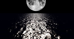 A 4K White colored moon setting slowly over the ocean at night with the color of the moon reflecting light onto the ocean waves stock video footage