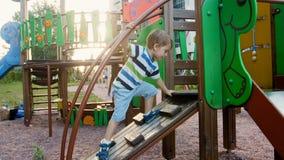 4k wideo śmieszny berbeć chłopiec pięcie na drewnianym stapladder na dziecka boisku przy parkiem zdjęcie wideo