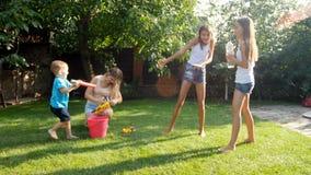 4k wideo cheeruful roześmiani dzieci z mateczną chełbotanie wodą nad each inny od wodnych pistoletów i ogrodowego węża elastyczne zdjęcie wideo