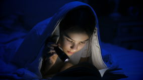 4k wideo dziewczyna czyta straszną opowieść pod koc przy nocą z latarką zbiory