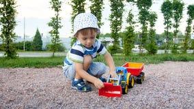 4k wideo 3 lat berbecia chłopiec bawić się na boisku z zabawkarskim ekskawatorem zdjęcie wideo
