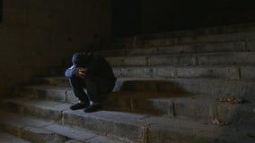 4K wideo lateral panning 24 fps młody desperacki zmizerowany mężczyzna w kapiszonu cierpieniu stresuje się drepression siedzieć n zbiory