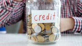4k wideo młodego pieniądze thowing pieniądze w szklanym słoju przylepiał etykietkę kredyt zdjęcie wideo