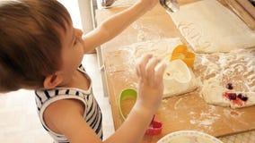 4k wideo mała śmieszna chłopiec bawić się z ciastem i składnikami na kuchni zdjęcie wideo