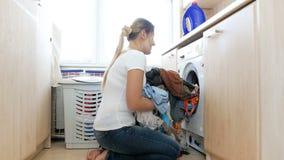 4k wideo piękny młodej kobiety brać czysty odziewa z pralki w łazience zbiory