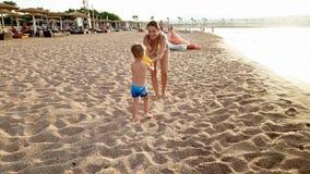 4k wideo rozochocona berbeć chłopiec i potomstwa matkujemy bawić się z piłką na morze plaży przy zmierzchem zdjęcie wideo