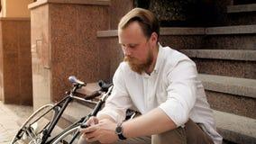 4k wideo uśmiechnięty czerwony brodaty mężczyzna obsiadanie na kamiennym schody i używać mądrze telefon zbiory