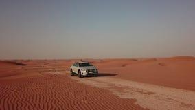 4K widok z lotu ptaka podąża nowego Tron w pustyni Abu dhabi U A e Elektryczny samochód w pustyni zbiory