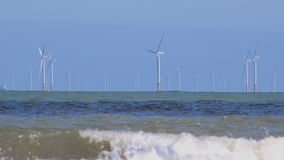 4K wind turbines in the ocean with waves foreground UK stock footage