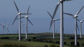 4K wind turbines hedgerows in farmers field blue sky summer day UK stock video