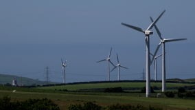 4K wind turbines in blue sky summer day power lines for electricity in background UK stock footage