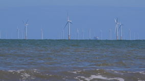 4K wind turbines in the ocean with waves foreground UK stock video footage