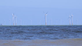 4K wind turbines in the ocean with waves foreground UK stock video