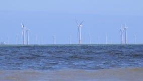4K windturbines in de oceaan met golvenvoorgrond het UK stock video