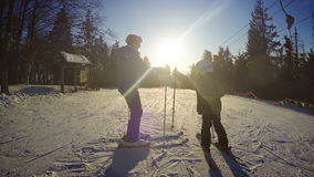 4K Winter holiday footage: son skiing with his mother during sunny day stock video footage