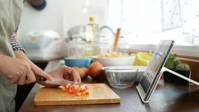 4K. woman slicing red tomato prepare ingredients for cooking follow cooking online video clip on website via tablet.