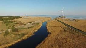 4K Wysoki lot nad błękitnymi polami w kierunku silników wiatrowych, rzeką i morzem i, widok z lotu ptaka przy zmierzchem zbiory wideo