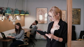 4k. young beautiful blonde businesswoman uses a touchscreen tablet in the modern startup office.