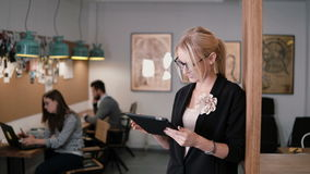 4k. young beautiful blonde businesswoman uses a touchscreen tablet in the modern startup office. 4k. beautiful blonde businesswoman uses a touchscreen tablet in Stock Image
