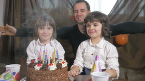 4k - Young beautiful girl blowing candles on a birthday cake with her father and twin sister stock video footage
